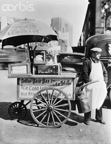 Hot Dog Vendor Standing Beside Cart
